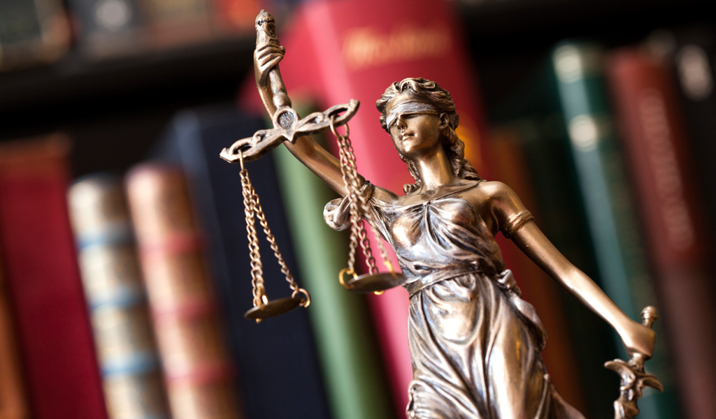 Statue of justice in front of legal books representing the legal right of people with ADHD