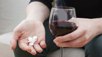 Man with ADHD holding medication in one hand and glass of wine in the other