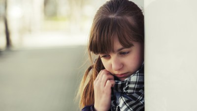 Girl with ADHD and depression at school leaning against wall and trying to cover face with scarf