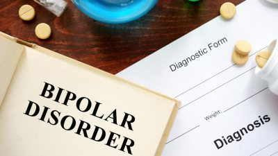 Book about bipolar disorder with diagnostic form next to it surrounded by different types of medication