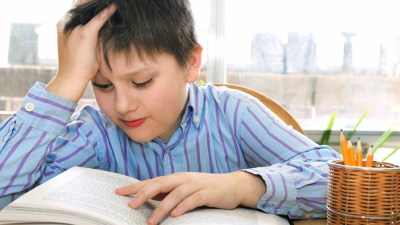 A child with both dysgraphia and ADHD, struggling to read a book