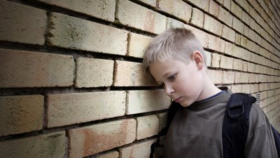 Boy with ADHD looking sad and leaning head against brick wall