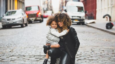 Mother holding daughter with ADHD on cobblestone street