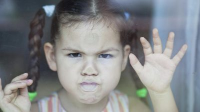 Little girl with ADHD angrily pressing face against glass door