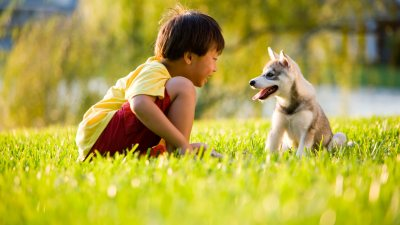 Little boy with ADHD sits outside on grass with pet puppy
