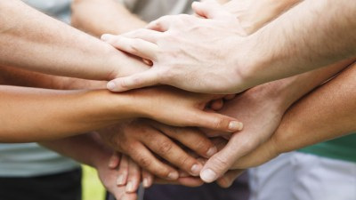 Hands stacked on top of each other in an encouraging ADHD support group for parents