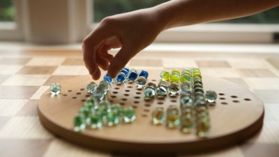 Close up of ADHD child's hand playing chinese checkers by window
