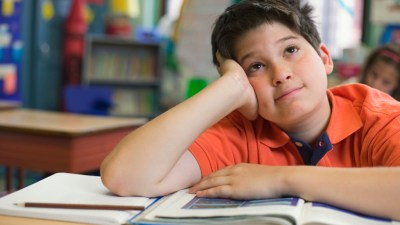 Boy with ADHD day dreaming at desk in classroom