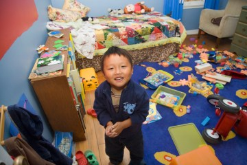 Boy with ADHD looks into camera smiling with pile of toys in a mess behind him