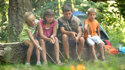 Kids with ADHD in woods around camp fire toasting marshmallows