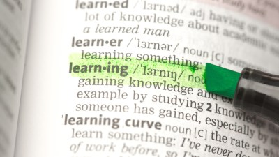 """Close up of word """"learning"""" highlighted in dictionary belonging to ADHD person"""