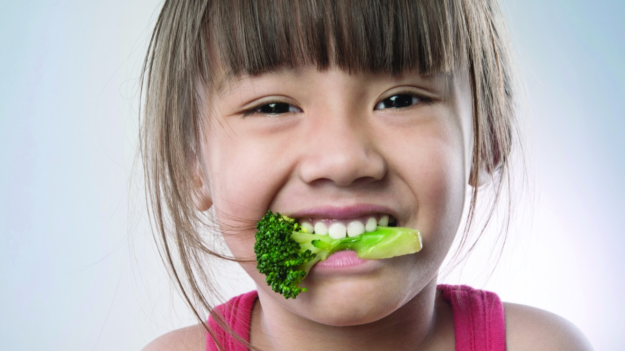A young girl chewing on a piece of broccoli, part of a healthy diet to help with ADHD
