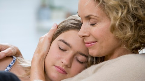 Mother holding daughter (13-15) eyes closed, smiling, close-up
