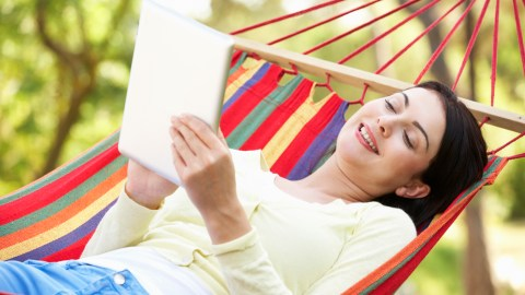 A woman relaxes in a hammock and reads an e-book, taking part in important self-care/