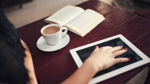 A woman rests her hand on a tablet and tries to stay on task reading a book while she drinks coffee.
