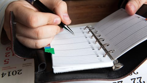 A man practices staying on task while writing things in his address book.