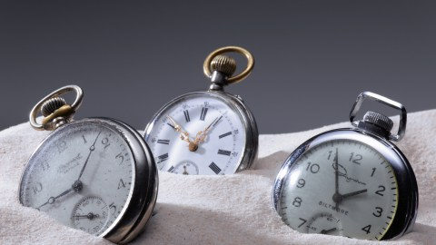 Three pocket watches in sand. People with impaired executive function need them to keep track of time.