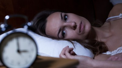Woman lying in bed suffering from sleeplessness