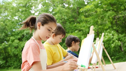Children painting outside during summer to slow down learning loss