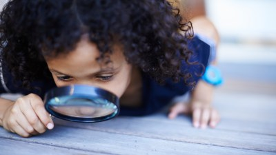 A child with SPD examines the ground with a magnifying glass.