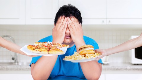 A man with ADHD covers his eyes to avoid seeing pizza and a burger, while he is trying to lose weight