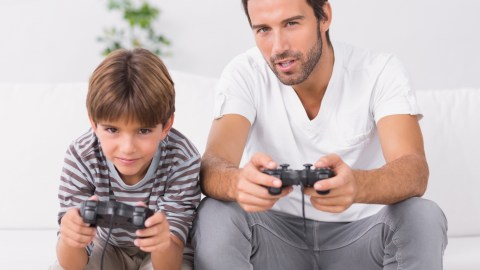 A father plays video games with his son. Spending quality time together is one strategy for how to be a better dad.