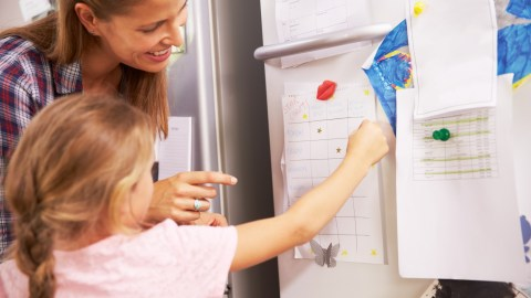Mother and daughter putting star on reward chart, easy system for kids
