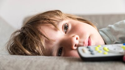 Girl with ADHD watching TV on couch and suffering from sleep issues