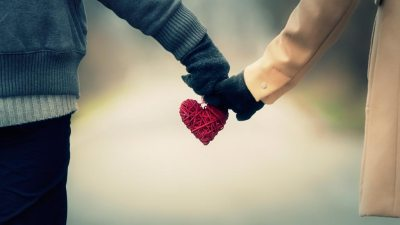 Married couple with ADHD hold hands on walk with ornament of heart in between them