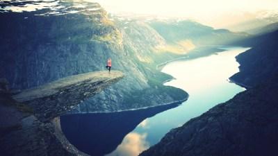 Woman with ADHD doing yoga on mountain ledge over lake