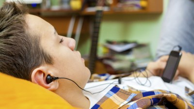 Teen boy with ADHD laying on pillow at home while listening to music with eyes closed