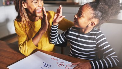 Mother high fives her ADHD child, success at doing homework