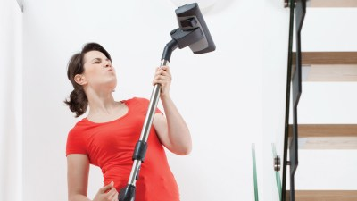 A woman dancing with her vacuum as she learns how to make chores fun