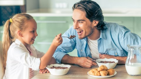 A girl with ADHD has breakfast with her father before school