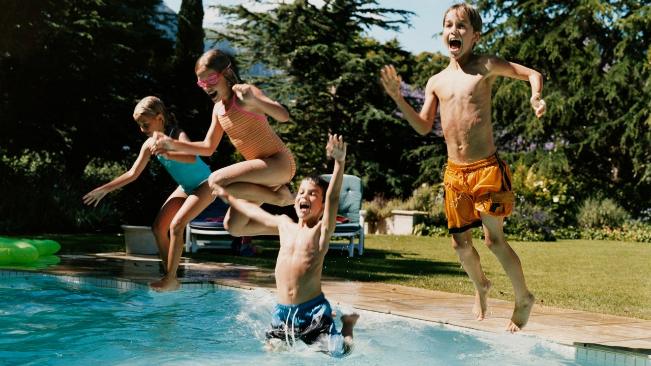 Four kids jump in a pool and yell, enjoying relaxed summer rules.