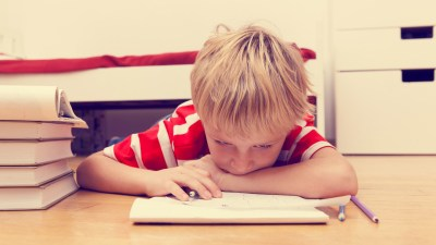 ADHD boy wondering if his medication is working as he does homework