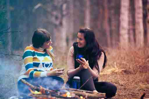 Two ADHD women friends catch up while camping outdoors
