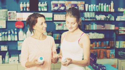 Mother helping her teenage daughter take responsibility for her own ADHD medication at a pharmacy