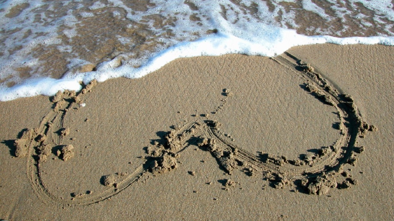 Heart in sand being washed away by waves, representing relationship issues of ADHD people