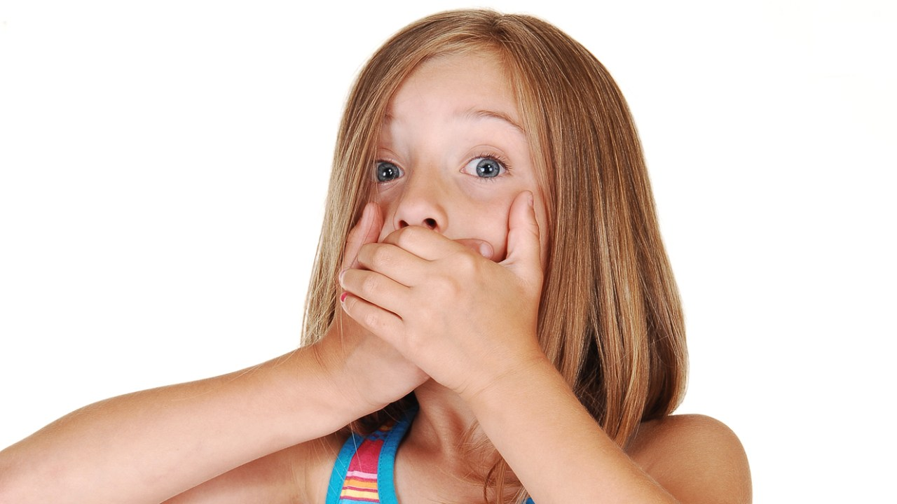 A girl with ADHD is covering her mouth because she doesn't know how to swallow a pill