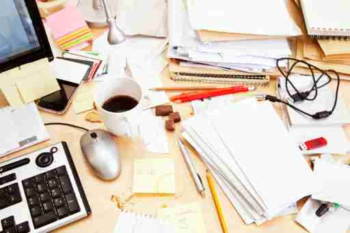 """A messy desk of someone with ADHD wondering, """"Am I going to get fired for being disorganized?"""""""