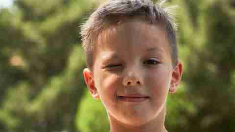 Boy with ADHD and a tic disorder winking