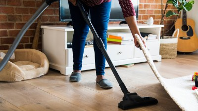 An adult with ADHD is cleaning the living room.