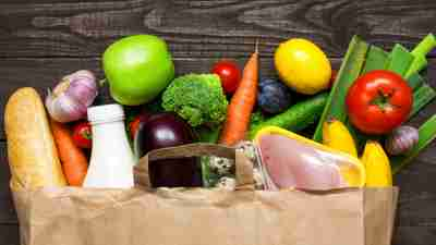 Healthy foods for ADHD brains spilling out of a paper grocery bag