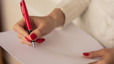 Female hands of ADHD woman with red nails write on a sheet of paper