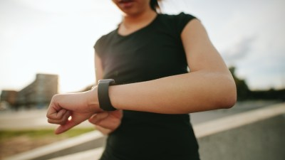 A woman using wristwatch technology to track progress