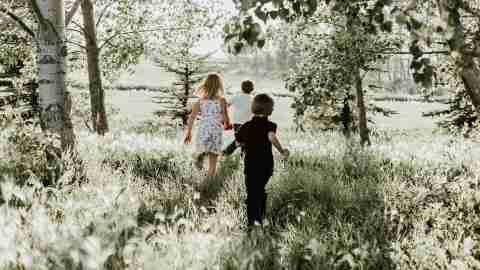 A group of siblings with ADHD runs through the trees