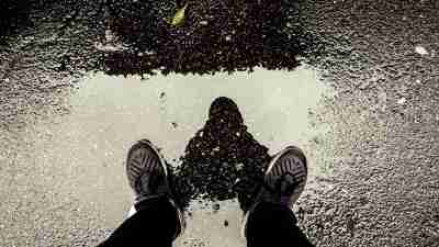 A man standing over a puddle which shows his reflection