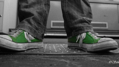 A boys wearing green Converse sneakers goes to school