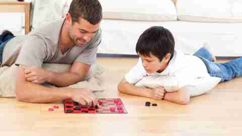 Father and son play checkers to learn executive functions.